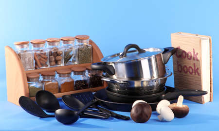 composition of kitchen tools,spices and cook book on blue background photo