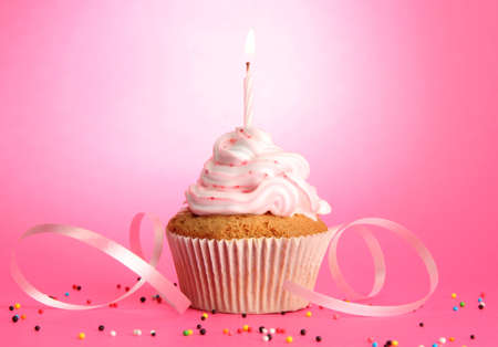 cup cakes: tasty birthday cupcake with candle, on pink background
