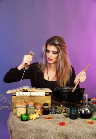 Halloween witch stirring in poison soup in her cauldron on color background Stock Photo
