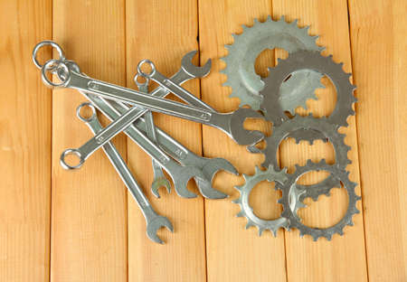 Metal cogwheels and spanners on wooden background Stock Photo - 17459014