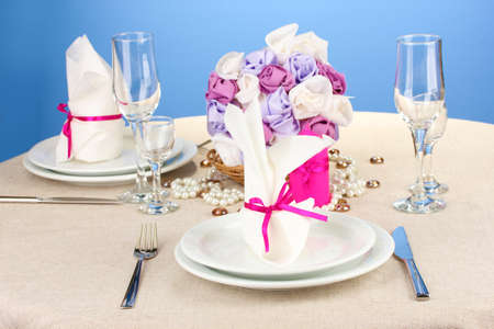 Table setting in purple tones on color  background photo