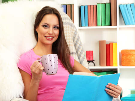 Portrait of female with cup of tea reading book at home photo