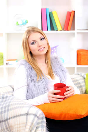 Attractive young woman sitting on sofa, holding cup with hot drink, on home interior background Stock Photo - 17761862