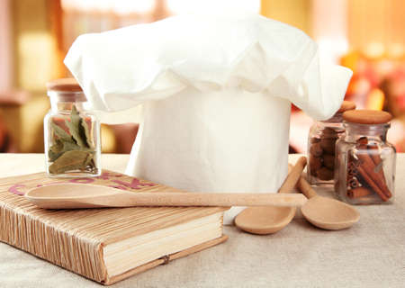 Chef's hat with spoons on table in kitchen Imagens