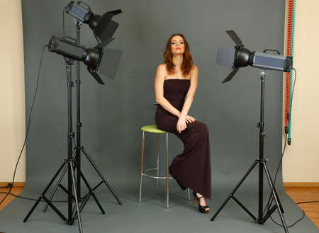 beautiful professional female model resting between shots in photography studio shoot set-up photo