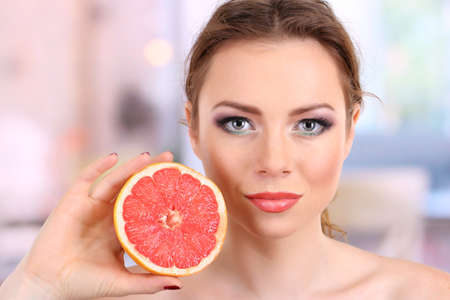 Beautiful young woman with bright make-up, holding grapefruit, on bright background photo