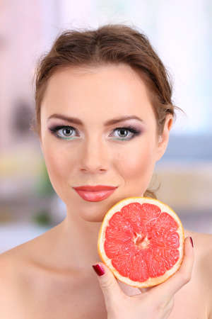 Beautiful young woman with bright make-up, holding grapefruit, on bright background Stock Photo - 17545312