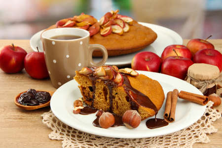 slice of tasty homemade pie with chocolate and apples and cup of coffee, on wooden table photo