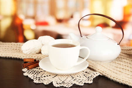 cup of tea with scarf on table in room photo