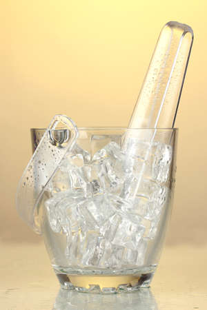 Glass ice bucket on light yellow background Stock Photo - 17515895