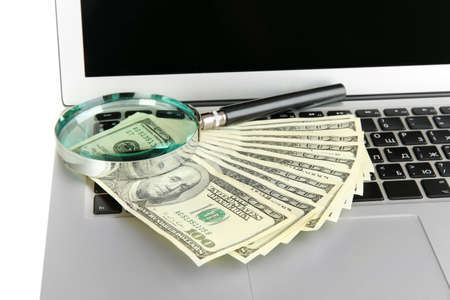 Money with magnifying glass on laptop close-up Stock Photo - 17516104