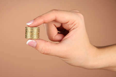 Woman hands with coins on brown background photo