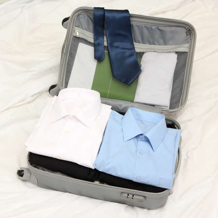 Open grey suitcase with clothing on bed Stock Photo - 17516514