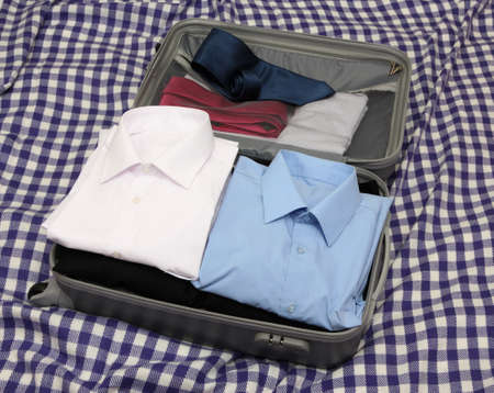 Open grey suitcase with clothing on plaid Stock Photo - 17516522