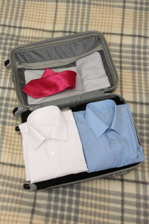 Open grey suitcase with clothing on plaid Stock Photo - 17516508