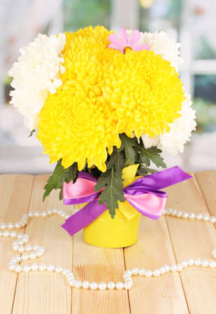 Beautiful chrysanthemum in pail on wooden table on window background Stock Photo - 17520254
