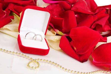 Beautiful box with wedding rings on red, white and pink rose petals background isolated on white Stock Photo - 17520335