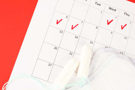 menstruation calendar with sanitary pads and tampons, close-up photo