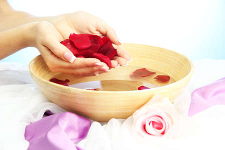 woman hands with wooden bowl of water with petals, on blue background photo