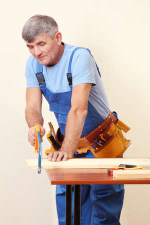 sawing: Builder sawing boards on table on wall background Stock Photo