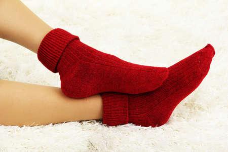 Weibliche Beine in bunten Socken auf weißem Teppich Hintergrund