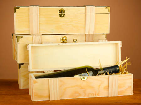 Wine bottle in wooden box on wooden table on brown background Stock Photo - 17519445