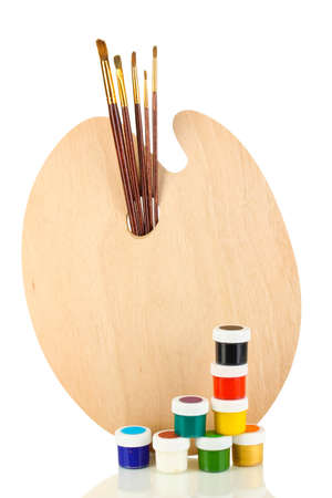 Wooden art palette with brushes for painting and paints isolated on white photo