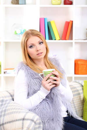 Attractive young woman sitting on sofa, holding cup with hot drink, on home interior background Stock Photo - 17761898
