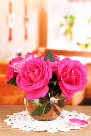 Beautiful pink roses in vase on wooden table on room background Stock Photo - 17520306