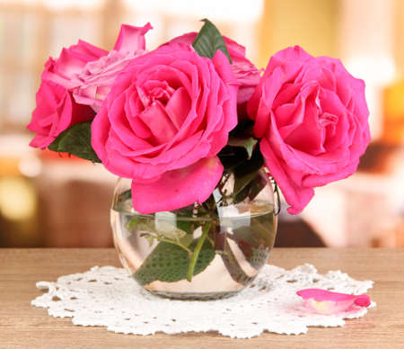 Beautiful pink roses in vase on wooden table on room background Stock Photo - 17517244