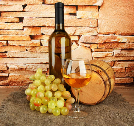 composition of wine,wooden barrel and grapes on table on brick wall background photo
