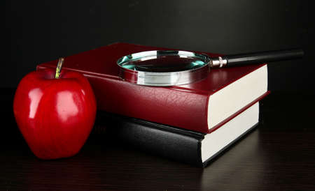 books with magnifying glass on table on black background photo