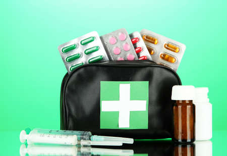 being the case: First aid bag, on green background Stock Photo