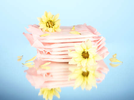 Panty liners in individual packing and yellow flowers on blue background close-up Stock Photo - 17527934