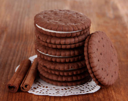 nutritiously: Chocolate cookies with creamy layer on wooden table close-up