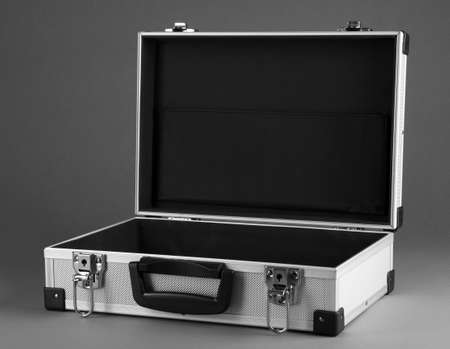 Opened silvery suitcase on grey background Stock Photo - 17527999