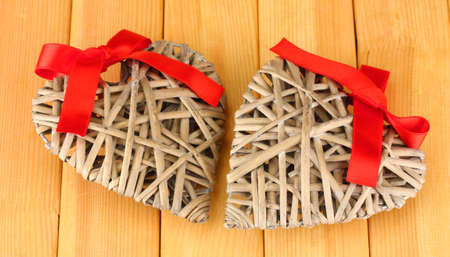 Wicker hearts with red bow on wooden background photo