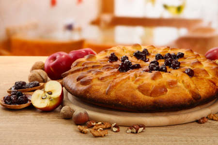 tasty homemade pie with jam and apples, on wooden table in cafe photo