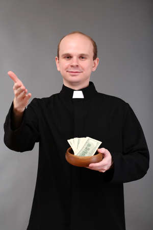 Young pastor with money on gray background Stock Photo