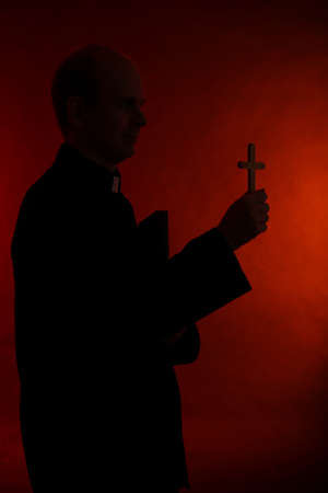 Young pastor with cross and Bible, on dark red background Stock Photo