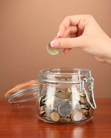 Saving, female hand putting a coin into glass bottle, on color background Stock Photo - 17542211