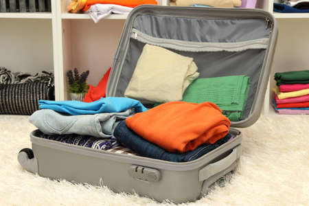 Open grey suitcase with clothing in room photo