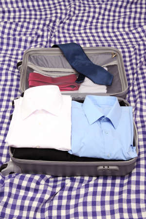 Open grey suitcase with clothing on plaid photo