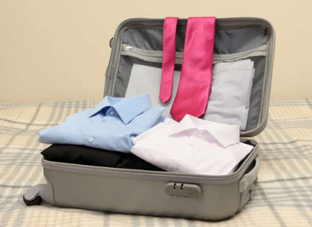 Open grey suitcase with clothing on bed Stock Photo - 17541878