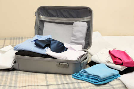 Open grey suitcase with clothing on bed Stock Photo - 17569685