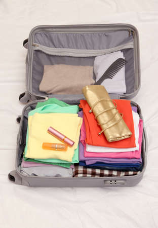 Open grey suitcase with clothing on bed Stock Photo - 17570566