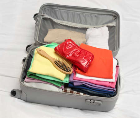 Open grey suitcase with clothing on bed Stock Photo - 17541519