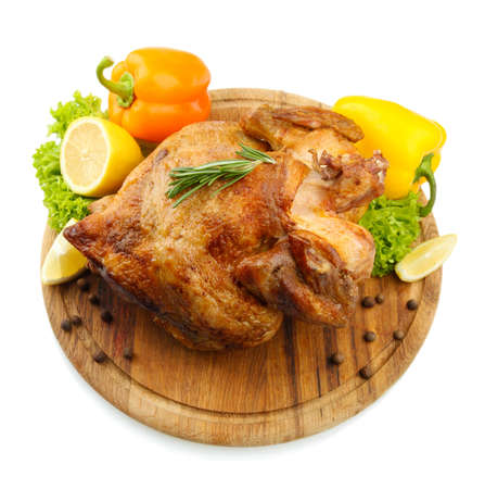 Whole roasted chicken on wooden plate with vegetables, isolated on white photo
