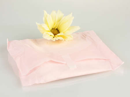 Panty liner in individual packing and yellow flower isolated on white Stock Photo - 17577949