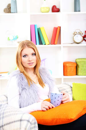 Attractive young woman sitting on sofa, holding cup with hot drink, on home inter background Stock Photo - 17761976